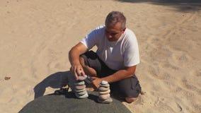 Bemannen Sie das Sitzen auf dem Sand und errichten Sie ausgeglichene Steinpyramide stock video