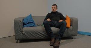 Bemannen Sie das Sitzen auf dem Sofa in der Lobby und die Aufwartung stock video
