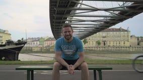 Bemannen Sie das Sitzen auf der Bank und das Lächeln zur Kamera gegen den Fluss stock footage