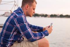 Bemannen Sie das Sitzen auf der Brücke nahe bei Meer und die Anwendung der Tablette Stockfoto