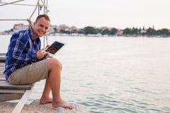 Bemannen Sie das Sitzen auf der Brücke nahe bei Meer und die Anwendung der Tablette Stockbild