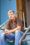 Bemannen Sie das Sitzen auf der Treppe von einem alten Lizenzfreies Stockfoto