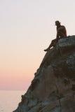 Bemannen Sie das Sitzen auf die Klippenoberseite auf dem Sonnenuntergang Lizenzfreies Stockfoto