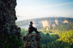 Bemannen Sie das Sitzen auf die Oberseite des Berges, Freizeit in Übereinstimmung mit Natur lizenzfreie stockfotos