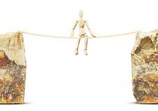 Bemannen Sie das Sitzen auf einem dünnen Bauholz zwischen zwei hohen Felsen Stockbild