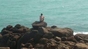 Bemannen Sie das Sitzen auf einem enormen Flussstein auf einem Strand und das Betrachten des Meeres stock video