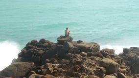 Bemannen Sie das Sitzen auf einem enormen Flussstein auf einem Strand und das Betrachten des Meeres stock video footage