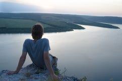 Bemannen Sie das Sitzen auf einem Felsen über dem Fluss bei Sonnenuntergang Stockbild