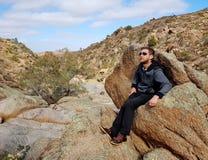 Bemannen Sie das Sitzen auf einem Felsen an Mannum-Wasserfällen Stockfotografie