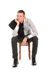Bemannen Sie das Sitzen auf einem Stuhl gegen einen weißen Hintergrund Lizenzfreies Stockfoto