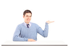 Bemannen Sie das Sitzen auf einer Tabelle und das Gestikulieren mit seiner Hand Stockbild