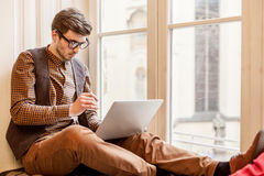 Bemannen Sie das Sitzen auf Fensterbrett und das Schreiben auf Laptop stockfotos