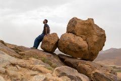Bemannen Sie das Sitzen auf großen Felsen am Rand eines Berges Stockfotos