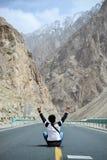 Bemannen Sie das Sitzen auf Landstraße in Xinjiang, China lizenzfreie stockbilder