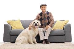 Bemannen Sie das Sitzen auf Sofa und die Aufstellung mit seinem Hund Stockfotografie
