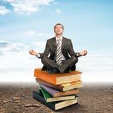Bemannen Sie das Sitzen auf Stapel von Büchern und das Meditieren Stockfoto