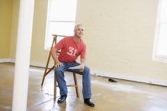 Bemannen Sie das Sitzen auf Strichleiter im leeren Platzholdingpapier Stockfotos