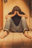 Bemannen Sie das Sitzen auf von Bodenfliesen, traurig, deprimiert und einsam Stockfotografie