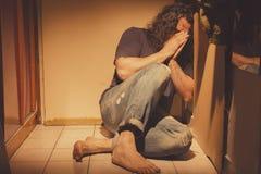 Bemannen Sie das Sitzen auf von Bodenfliesen, traurig, deprimiert und einsam Lizenzfreies Stockbild