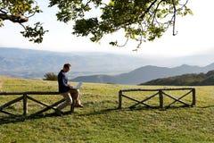 Bemannen Sie das Sitzen auf Zaun in der Landschaft unter Verwendung des Laptops Lizenzfreie Stockfotos
