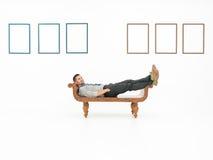 Bemannen Sie das Sitzen in der Kunstgalerie mit leeren Rahmen Lizenzfreie Stockfotografie