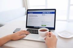 Bemannen Sie das Sitzen an der MacBook-Retina mit Standort Facebook auf dem scre Stockfotos