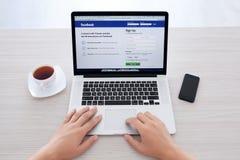 Bemannen Sie das Sitzen an der MacBook-Retina mit Standort Facebook auf dem scre Lizenzfreie Stockbilder