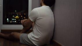 Bemannen Sie das Sitzen durch ein Fenster und Nacht niedergedrückt und traurig betrachten stock video