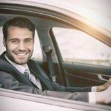 Bemannen Sie das Sitzen in einem Auto, das Kamera lächelt und betrachtet Lizenzfreie Stockfotos