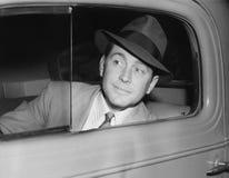 Bemannen Sie das Sitzen in einem Auto, welches heraus das Fenster schaut (alle dargestellten Personen sind nicht längeres lebende Lizenzfreie Stockbilder