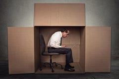 Bemannen Sie das Sitzen in einem Kasten, der auf Laptop-Computer arbeitet Lizenzfreie Stockfotos