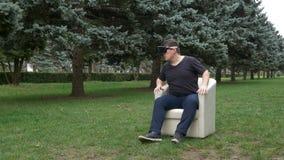 Bemannen Sie das Sitzen in einem Lehnsessel im Park, der Umgebungen mit Kopfhörer der virtuellen Realität - VR betrachtet stock video footage