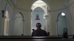 Bemannen Sie das Sitzen in einer Bank an der Kirche und am Meditieren, Glauben- und Religionskonzept stock footage