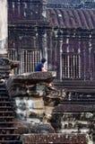 Bemannen Sie das Sitzen im Angkor Wat und das Schauen zur Wand Lizenzfreies Stockfoto