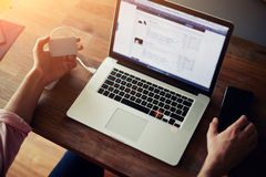 Bemannen Sie das Sitzen im Büro an einem Schreibtisch, der auf einem Computer arbeitet Lizenzfreies Stockbild