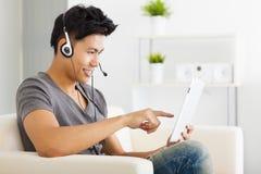 Bemannen Sie das Sitzen im Sofa und die Anwendung von Tabletten-PC Stockfoto