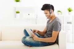 Bemannen Sie das Sitzen im Sofa und die Anwendung von Tabletten-PC Stockbild