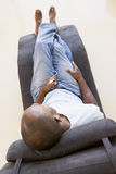 Bemannen Sie das Sitzen im Stuhl, der zum MP3-Player hört Stockbilder