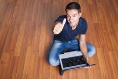 Bemannen Sie das Sitzen mit Laptop und mit seinem Daumen oben lizenzfreie stockfotografie