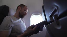 Bemannen Sie das Sitzen nahe dem Fenster des Fliegenflugzeug- und Lesezeitschriftenvorratgesamtlängenvideos stock footage