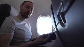 Bemannen Sie das Sitzen nahe dem Fenster des Fliegenflugzeug- und Lesezeitschriftenvorratgesamtlängenvideos stock video