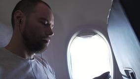 Bemannen Sie das Sitzen nahe dem Fenster des Fliegenflugzeuges und das Hören Musik auf Kopfhörern mit Ihrem Smartphone Gesamtläng stock video footage
