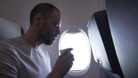 Bemannen Sie das Sitzen nahe dem Fenster des Fliegenflugzeuges und das Trinken eines Getränks aus Papierschalen-Vorratgesamtlänge stock video