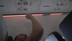 Bemannen Sie das Sitzen nahe Fensterfliegenflugzeug und reguliert den Fluss der Luft vom persönlichen Conditionervorrat-Gesamtlän stock footage