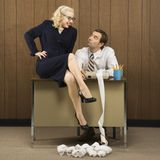 Bemannen Sie das Sitzen am Schreibtisch, der die Frau betrachtet, die auf Schreibtisch sitzt. stockfoto