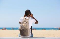 Bemannen Sie das Sitzen am Strand mit Tasche und Kopfhörern lizenzfreie stockbilder