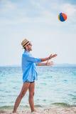 Bemannen Sie das Spielen auf dem Strand mit einem Ball Lizenzfreies Stockfoto