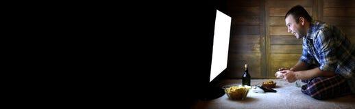 Bemannen Sie das Spielen auf einer Konsole auf dem Steuerknüppel vor dem großen Fernsehgeröll lizenzfreie stockfotografie