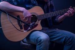 bemannen Sie das Spielen der Akustikgitarre auf einem schwarzen Hintergrund, das Musikkonzept, schöne Beleuchtung auf dem Stadium Stockfoto