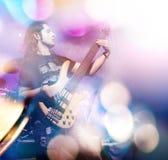 Bemannen Sie das Spielen der Bass-Gitarre in der Livekonzertreihenfolge Weinlesemikrofon und -öffentlichkeit Lizenzfreie Stockfotos